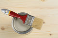 Paintbrush and a can with wood stain against wooden surface Royalty Free Stock Photography