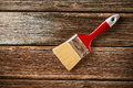 Paintbrush with red handle on the wooden table Royalty Free Stock Photos