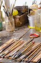 Paintbrushes in an atelier many on a messy table Royalty Free Stock Image
