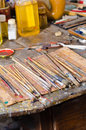 Paintbrushes in an atelier and oils many on a messy table Royalty Free Stock Images