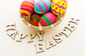 Painted easter egg in basket with wooden text Royalty Free Stock Images