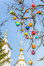 Painted Easter eggs on a tree branch. The Church in the background Royalty Free Stock Photo