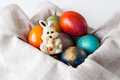 Painted easter eggs and white chocolate bunny on a linen cloth Royalty Free Stock Images