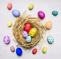 Painted with the faces of family members decorative eggs for Easter, in the nest wooden rustic background top view close up Royalty Free Stock Photo