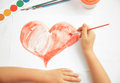 Painted heart unrecognizable child paints red Stock Photo