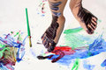 Painted kid s feet on art project a young child are covered in colorful paint as they are standing a white piece of paper covered Royalty Free Stock Images