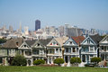 The painted ladies in alamo square at san francisco with a view of skyscrapers of downtown san francisco behind Stock Photos