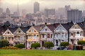 The painted ladies of san francisco california sit glowing amid backdrop a sunset and skyscrapers Royalty Free Stock Photo