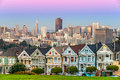 The painted ladies of san francisco california sit glowing amid backdrop a sunset and skyscrapers Royalty Free Stock Images