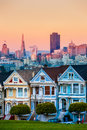 The painted ladies of san francisco california sit glowing amid backdrop a sunset and skyscrapers Royalty Free Stock Image