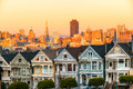 The painted ladies of san francisco california sit glowing amid backdrop a sunset and skyscrapers Stock Photography