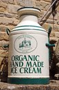 Painted milk churn organic hand made ice cream onto an old outside the entrance to the old mill lower slaughter cotswolds Stock Photo