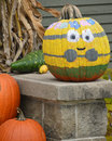 Painted minion pumpkin a hand to look like a with flowers around the top Royalty Free Stock Photos