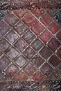 Painted in red shabby, scratched and rusty metal sheet and nailed to it tin strips in form of rhombus. Royalty Free Stock Photo