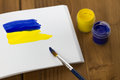 Painted ukrainian flag on sketchbook with colorful paint tubes and brush wooden background Royalty Free Stock Photography
