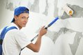 Painter at home renovation work with prime one paint roller making wall coating repair Royalty Free Stock Photography