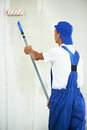 Painter at home renovation work with prime one paint roller making wall coating repair Royalty Free Stock Images