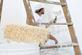 Painter man at work with paint roller, wall painting concept Royalty Free Stock Photo