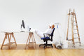 Painter man after work rests on the desk, weekend conc Royalty Free Stock Photo