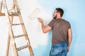 Painter in paint splattered shirt painting a wall Royalty Free Stock Photo