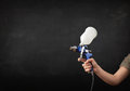 Painter works with airbrush gun and empty copyspace on dark background Stock Image