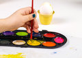 Painting egg little girls hands playing with colorful paint creating easter decoration Royalty Free Stock Images