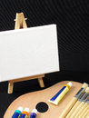 Painting essentials an image of paint brushes laying on a painters palette with an easel in the background Royalty Free Stock Image