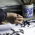Painting an old artist holding a chinese brush retouching his work Stock Photos
