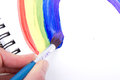 Painting of rainbow on notebook close up or sketch book with paintbrush Royalty Free Stock Image