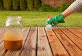 Painting wooden deck applying protective varnish on a patio floor Stock Image