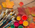 Paints, brushes, autumn leaves on wooden background. Royalty Free Stock Photo