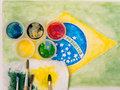 Paints lids brushes and and stained fabric on the brazil flag wa with watercolor painting motto ordem e progresso Royalty Free Stock Image