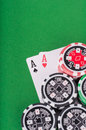 Pair of aces, red and black cassino chips on green table Royalty Free Stock Photo