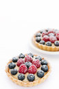 Pair of appetising fruit tarts yummy mix berry dusted with icing sugar Stock Photos