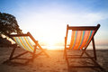 Pair of beach loungers on the deserted coast sea, perfect vacation concept. Royalty Free Stock Photo