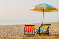 Pair of beach loungers on the deserted coast vacation concept in morning Royalty Free Stock Image