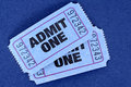 Pair of blue admit one movie tickets on a blue background. Royalty Free Stock Photo