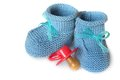 Pair of blue knit children's bootees and baby's dummy on a white background Royalty Free Stock Photo