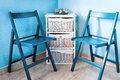 Pair of blue wooden chairs and small white commode near the wall
