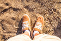 Pair of boots on sand shoes man s foot a sea side beach view from above summer leisure time background Stock Photo