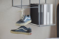 Pair of casual blue sneaker shoes hanging on book shelf Royalty Free Stock Photo