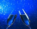 A pair of champagne flutes on blue light bokeh background make cheers with space for text Royalty Free Stock Image