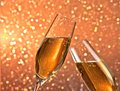 Pair of a champagne flutes with gold bubbles on light bokeh background Royalty Free Stock Photo