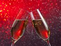 Pair of a champagne flutes with gold bubbles on red and violet light bokeh background Royalty Free Stock Photo