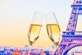 A pair of champagne flutes with golden bubbles on blur tower Eiffel background Royalty Free Stock Photo