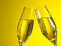 A pair of champagne flutes with golden bubbles on yellow light background make cheers space for text Stock Image