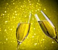 A pair of champagne flutes with golden bubbles on yellow light bokeh background make cheers Royalty Free Stock Image