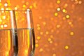 Pair of a champagne flutes on orange and yellow light bokeh background with space for text Stock Images
