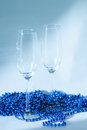 Pair of champagne glasses with a beautiful new year decoration festive blue beads chain on the homogeneous background Royalty Free Stock Photography