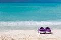 Pair of colored sandals on a white sand beach in front the sea the right place for relaxation and vacations Royalty Free Stock Photography